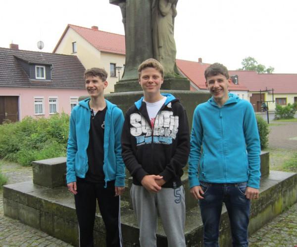 Kriegerdenkmal mit Interviewern: Sebastian Berg, John und Leon Wedig