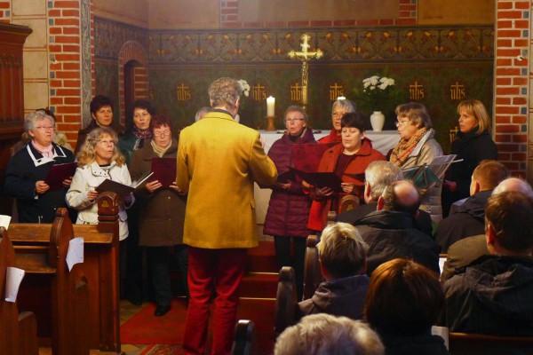 Der Singkreis singt unter dem Kreuz.