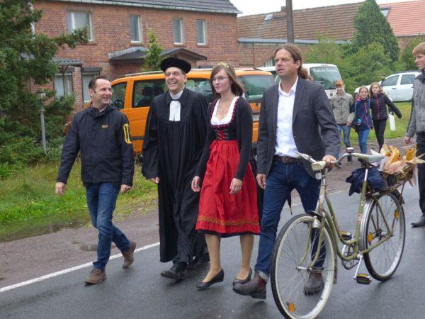 Amtsdirektor Pfarrer Erntekoenigin und Buergermeister gehen voran beim Erntefestumzug