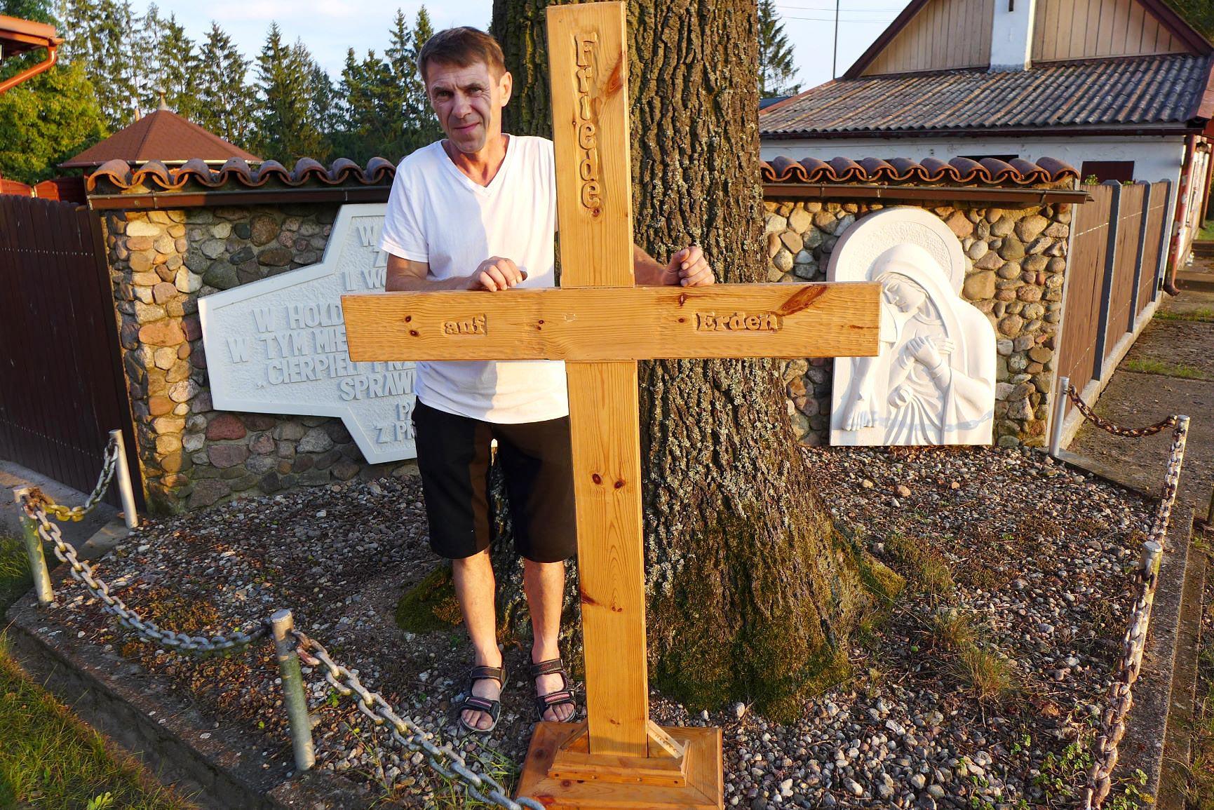 Sylvester Wotsch mit reparierten Friedenskreuz vor dem Denkmal des von den Deutschen ermordeten Priesters - Titanen on tour 2018