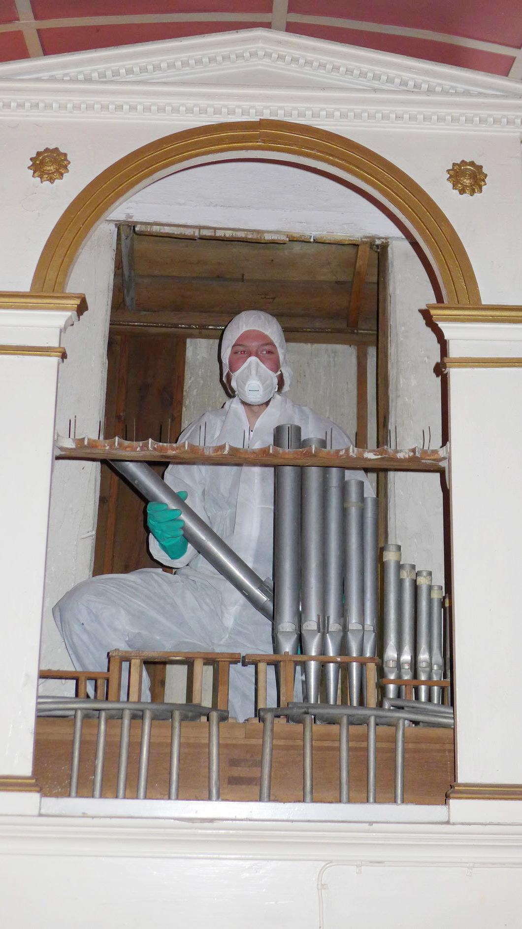 Monteur der Firma Schuke im vollschutz gegen DDT mit Orgelpfeifen - Eselpilgerlichtkirche Neuendorf