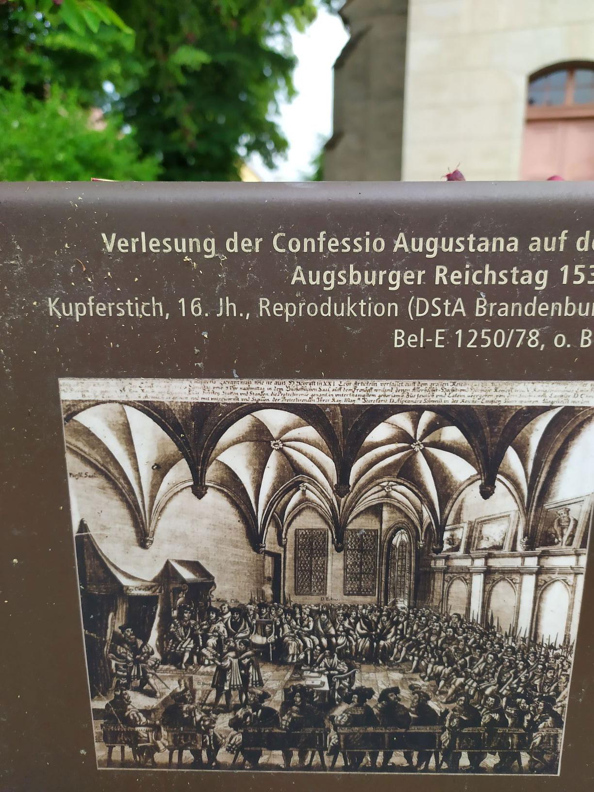 Bild vom Augsburger Reichstag an Stadtmöbel vor der Lambertuskirche